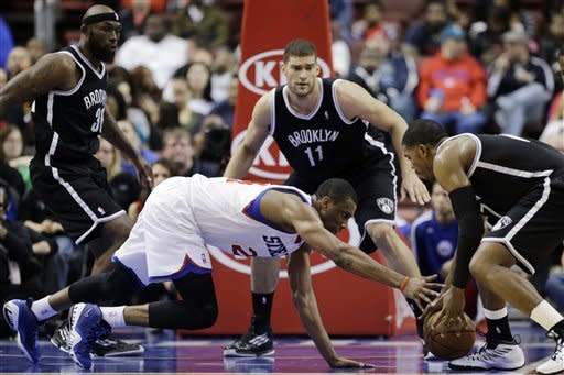 Philadelphia 76ers' Thaddeus Young (21) dives for a loose ball against Brooklyn Nets' Joe Johnson (7) as Reggie Evans (30) and Brook Lopez (11) watch during the first half of an NBA basketball game, Monday, March 11, 2013, in Philadelphia. (AP Photo/Matt Slocum)