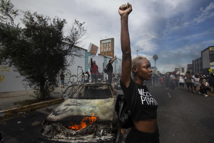 A protester raises her fist in the air next to a burning police vehicle in Los Angeles, May 30, 2020, during a demonstration over the death of George Floyd. The image was part of a series of photographs by The Associated Press that won the 2021 Pulitzer Prize for breaking news photography. (AP Photo/Ringo H.W. Chiu)