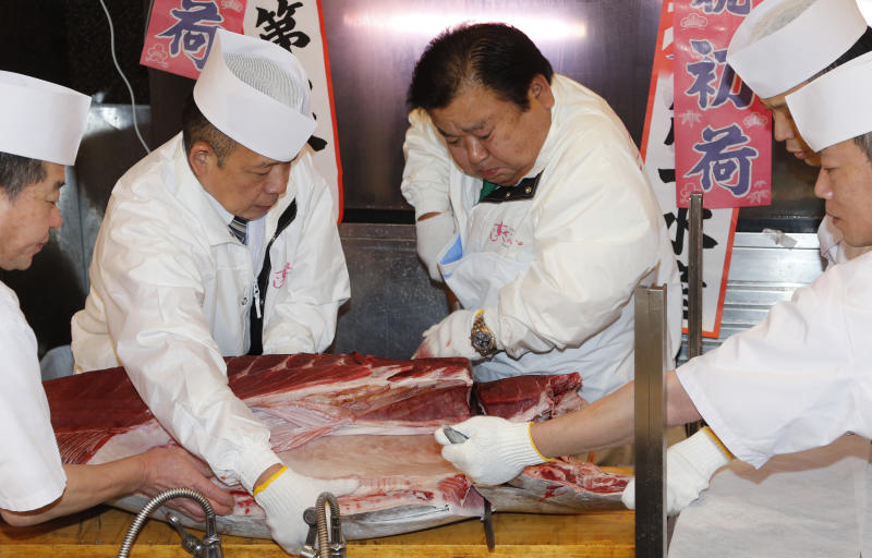 Sushi restauranteur Kiyoshi Kimura, second from right, cuts a 507-pound (230-kilogram) bluefin tuna he bought at the year's celebratory first auction at his restaurant near Tsukiji fish market in Tokyo, Sunday, Jan. 5, 2014. Kimura paid 7.36 million yen (about $70,000) for the bluefin tuna in the auction, just one-twentieth of what he paid a year earlier despite signs the species is in serious decline. (AP Photo/Shizuo Kambayashi)