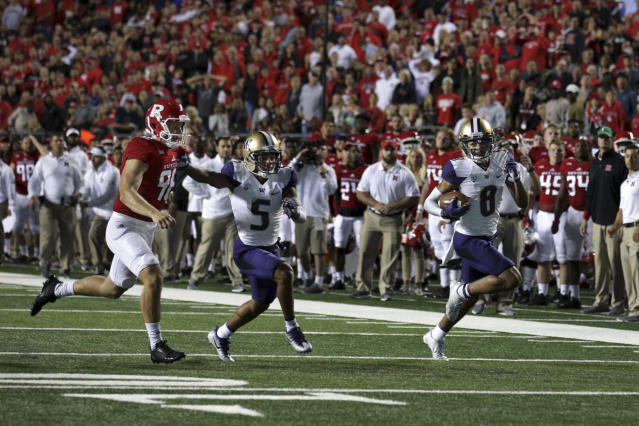 "Washington wide receiver <a class=""link rapid-noclick-resp"" href=""/ncaaf/players/244153/"" data-ylk=""slk:Dante Pettis"">Dante Pettis</a> (8) runs a punt-return for a touchdown as as Andre Baccellia (5) blocks Rutgers punter <a class=""link rapid-noclick-resp"" href=""/nfl/players/30162/"" data-ylk=""slk:Ryan Anderson"">Ryan Anderson</a> during the first half of an NCAA college football game Friday, Sept. 1, 2017, in Piscataway, N.J. (AP Photo/Mel Evans)"