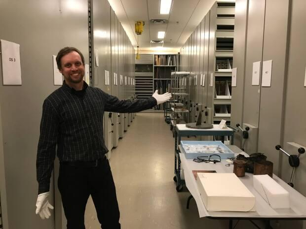 Ryan Silke is the curatorial assistant at the Prince of Wales Northern Heritage Centre. The museum recently offered guided tours of its storeroom collection — where the 95 per cent of its collection that's not on display is kept. (Alyssa Mosher/CBC - image credit)