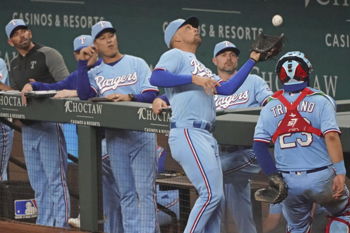 Texas Rangers first baseman Nathaniel Lowe catches a foul pop fly by Seattle Mariners' Dylan Moore near the Rangers' dugout in the seventh inning of a baseball game Sunday, Aug.1, 2021, in Arlington, Texas. (AP Photo/Louis DeLuca)