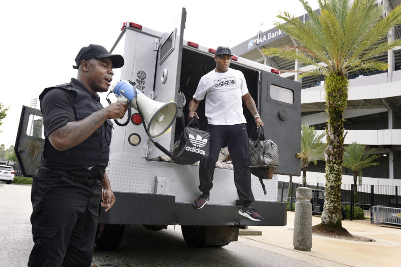 Comedian Ha Ha Davis, left, announces the arrival of Jacksonville Jaguars cornerback Jalen Ramsey to NFL football training camp as he steps from the back of an armored car outside TIAA Bank Field in Jacksonville, Fla., Wednesday, July 24, 2019. (Bob Self/The Florida Times-Union via AP)