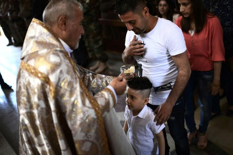 Father Sharbel Aisso blesses a child during Easter mass at the Mar Yohanna church in the predominantly Christian Iraqi town of Qaraqosh on April 16, 2017