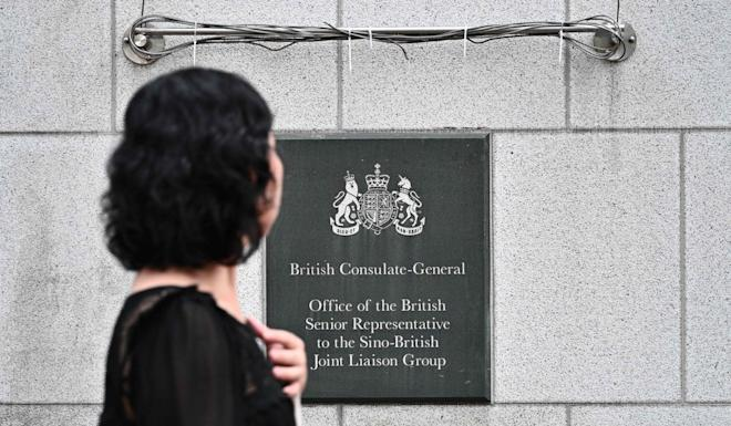 A pedestrian walks past a plaque outside the British Consulate-General building in Hong Kong, where Simon Cheng worked. Photo: AFP