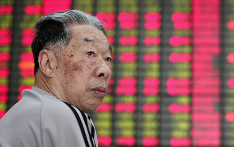 An investor looks at the stock price monitor at a private securities company Wednesday, July 4, 2012 in Shanghai, China. Global stocks were muted Wednesday in holiday-thinned trade as markets looked to European central bankers for new steps to buoy sluggish economic growth. (AP Photo)