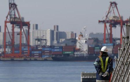 A worker walks near a container area at a port in Toky