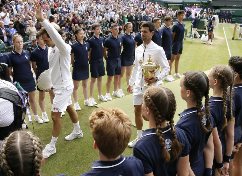 Serbia's Novak Djokovic, right, and Switzerland's Roger Federer leave the court holding their trophies after the men's singles final match of the Wimbledon Tennis Championships in London, Sunday, July 14, 2019. (AP Photo/Tim Ireland)
