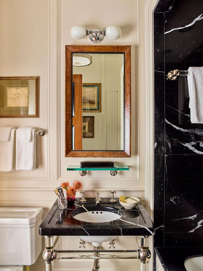 """<div class=""""caption""""> The bath echoes the apartment's traditional aesthetic with a glass-leg sink stand from <a href=""""http://www.urbanarchaeology.com/"""" rel=""""nofollow noopener"""" target=""""_blank"""" data-ylk=""""slk:Urban Archaeology"""" class=""""link rapid-noclick-resp"""">Urban Archaeology</a>; faucets from <a href=""""https://barberwilsons.com/"""" rel=""""nofollow noopener"""" target=""""_blank"""" data-ylk=""""slk:Barber Wilsons"""" class=""""link rapid-noclick-resp"""">Barber Wilsons</a>; a custom mirror designed by Schafer; and a toilet, tub, and sconce by <a href=""""https://www.waterworks.com/us_en/"""" rel=""""nofollow noopener"""" target=""""_blank"""" data-ylk=""""slk:Waterworks"""" class=""""link rapid-noclick-resp"""">Waterworks</a>. The tub enclosure and sink countertop add contrast to wood paneling in <a href=""""https://www.benjaminmoore.com/en-us"""" rel=""""nofollow noopener"""" target=""""_blank"""" data-ylk=""""slk:Benjamin Moore"""" class=""""link rapid-noclick-resp"""">Benjamin Moore</a>'s Seapearl thanks to Nero Marquina marble. </div>"""