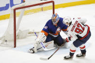 Washington Capitals center Evgeny Kuznetsov (92) and New York Islanders goaltender Semyon Varlamov (40) look into the net after Kuznesov scored in the shootout of an NHL hockey game,Thursday, April 22, 2021, in Uniondale, N.Y. The Capitals won 1-0. (AP Photo/Kathy Willens)