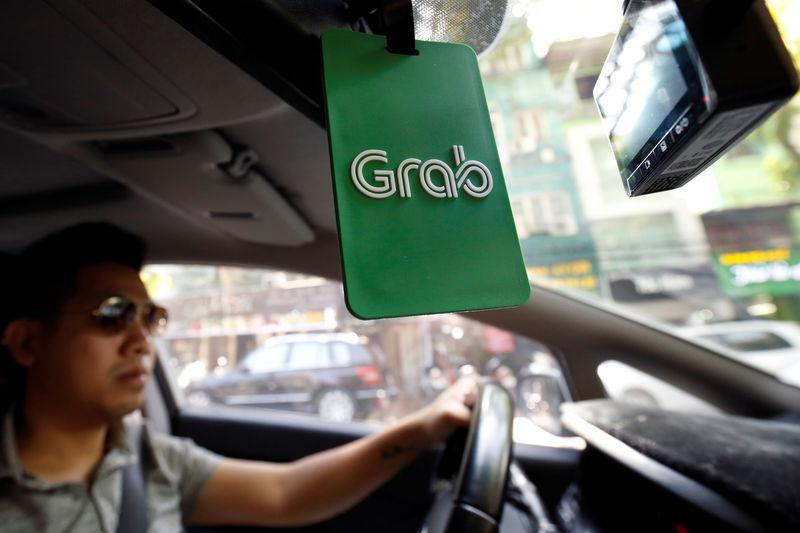 A Grab taxi drives on a street in Hanoi