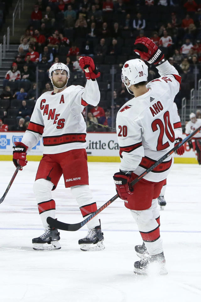 Carolina Hurricanes center Sebastian Aho (20) celebrates his third-period goal against the Detroit Red Wings with right wing Justin Williams, left, in an NHL hockey game Tuesday, March 10, 2020, in Detroit. (AP Photo/Duane Burleson)