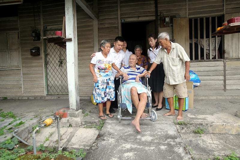Low and colleagues help the Ng siblings as they leave their dilapidated family home.