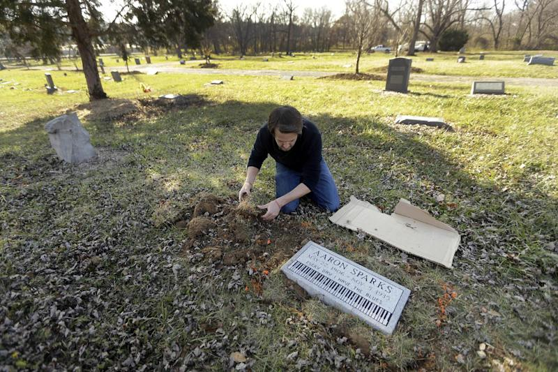 In this Dec. 4, 2013 photo, Aaron Pritchard replaces grass after laying a headstone on the previously unmarked grave of blues musician Aaron Sparks in Crestwood, Mo. Pritchard is part of the Killer Blues Headstone Project, a nonprofit effort to posthumously honor sometimes long-forgotten blues musicians with grave markers. The group has laid 22 headstones to date, with several more complete but awaiting placement. (AP Photo/Jeff Roberson)