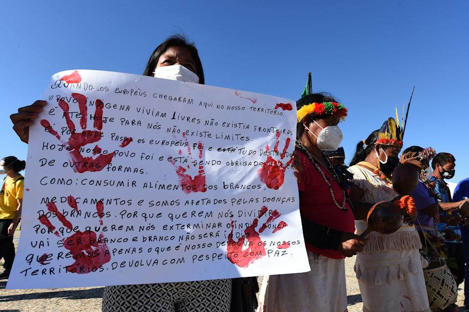 Indigenous people of different ethnicities protest against a controversial land reform bill, outside the Supreme Court in Brasilia on June 30, 2021. - The Supreme Court reviews a controversial bill that would change the regulations establishing protected indigenous lands. Indigenous rights groups warn the bill would pave the way for things such as mining, hydroelectric dams and road construction on previously protected reserves. (Photo by EVARISTO SA / AFP) (Photo by EVARISTO SA/AFP via Getty Images)