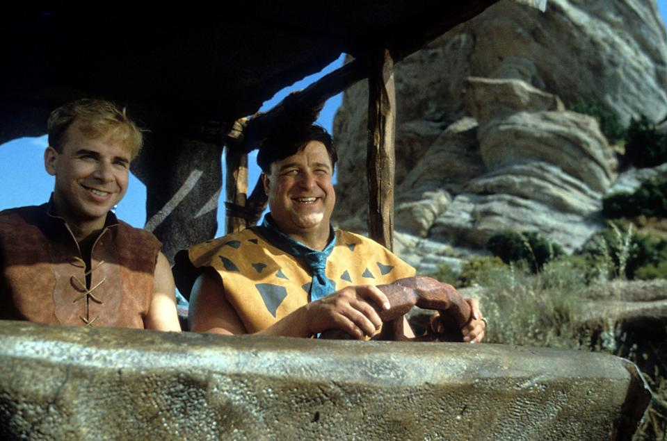 Rick Moranis and John Goodman riding together in a scene from the film 'The Flintstones', 1994. (Photo by Universal/Getty Images)