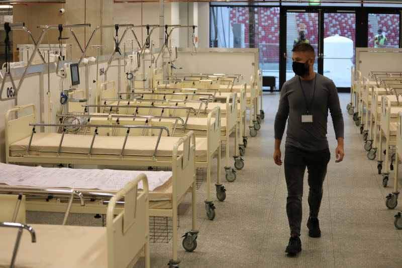 Man walks inside PGE National Stadium where the government builds a field hospital in Warsaw