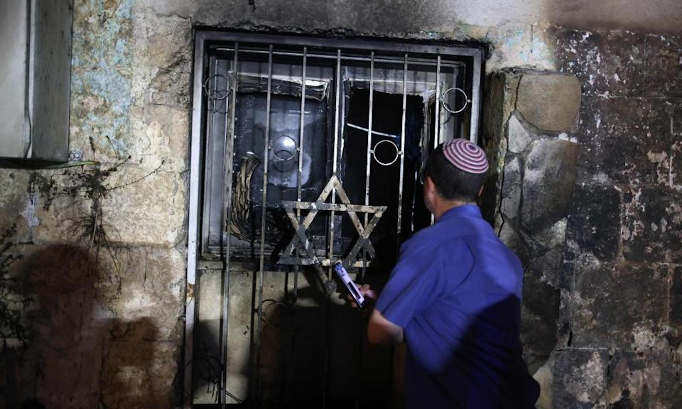 An Israeli man looks inside a synagogue after it was set on fire by Arab-Israelis in Lod.
