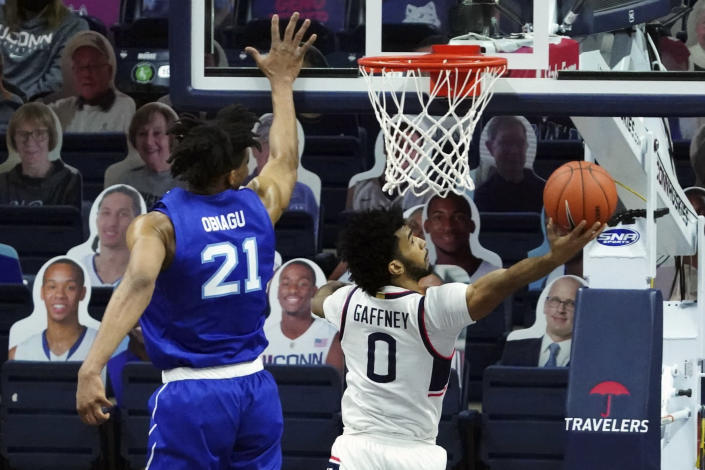 Connecticut's Jalen Gaffney (0) makes a basket against Seton Hall center Ike Obiagu (21) during the second half of an NCAA college basketball game, Saturday, Feb. 6, 2021, at Harry A. Gampel Pavilion in Storrs, Conn. (David Butler II/Pool Photo via AP)