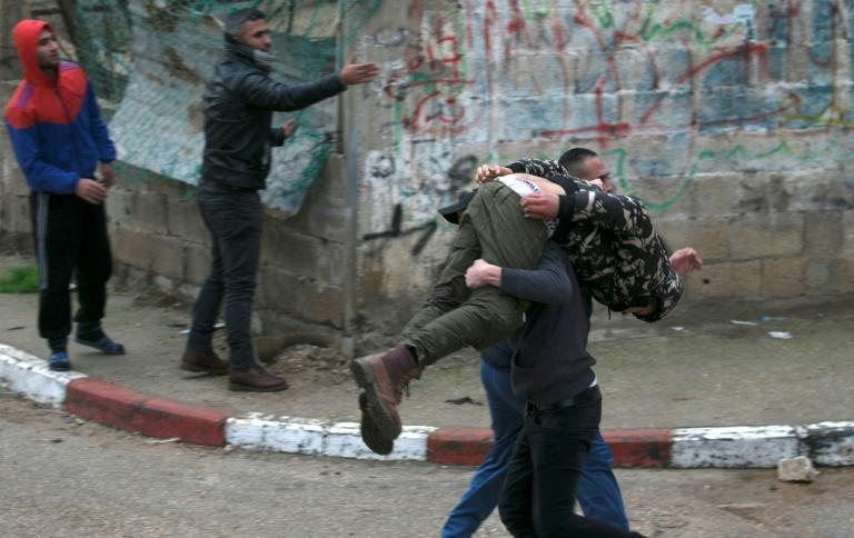 Palestinian youths evacuate a wounded comrade during clashes with Israeli forces in the northern West Bank city of Jenin on January 18, 2018 in which a wanted murder suspect was killed