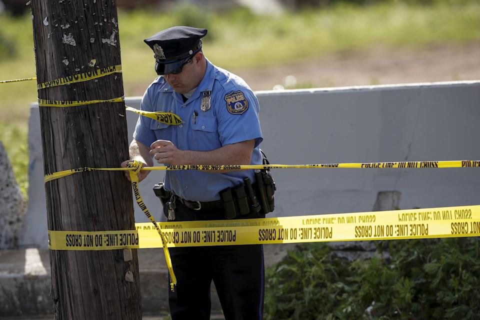 A police officer creates a cordon at the site of a derailed Amtrak train in Philadelphia, Pennsylvania May 13, 2015. Rescue workers searched through the debris on Wednesday for more victims of an Amtrak passenger train wreck in Philadelphia that killed six people and injured scores others as investigators sought to determine the cause of the derailment. Authorities said they did not know what caused the New York City-bound train carrying 243 people to derail at about 9:30 p.m. EDT Tuesday (0130 GMT Wednesday). The accident left rail cars mangled, ripped open and strewn upside down in the city's Port Richmond neighborhood along the Delaware River. REUTERS/Mike Segar