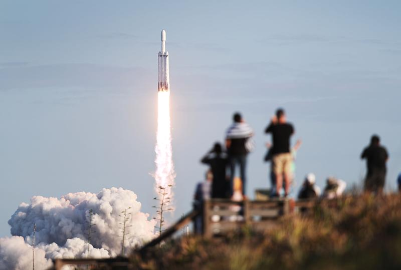 TITUSVILLE, FLORIDA - APRIL 11: People watch as the SpaceX Falcon Heavy rocket lifts off from launch pad 39A at NASA's Kennedy Space Center on April 11, 2019 in Titusville, Florida. The rocket is carrying a communications satellite built by Lockheed Martin into orbit. (Photo by Joe Raedle/Getty Images)