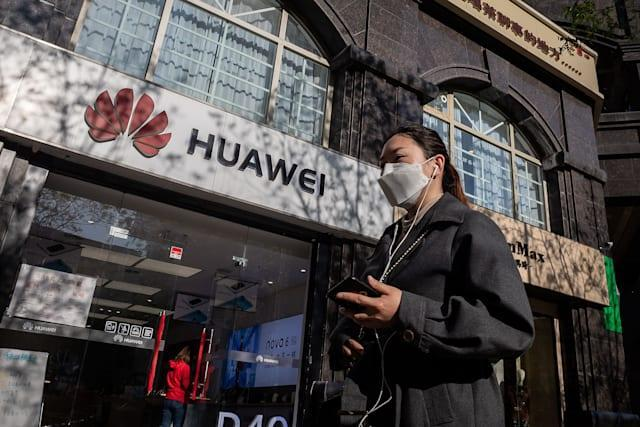A woman wearing a face mask amid concerns over the COVID-19 coronavirus walks holding her smartphone past a Huawei shop (L) on a street in Beijing on April 22, 2020. - China's economy shrank for the first time in decades last quarter as the coronavirus paralysed the country, in a historic blow to the Communist Party's pledge of continued prosperity in return for unquestioned political power. (Photo by NICOLAS ASFOURI / AFP) (Photo by NICOLAS ASFOURI/AFP via Getty Images)