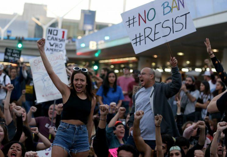 Protesters hold signs as they block a road during a demonstration against the immigration ban imposed by Trump at Los Angeles International Airport on Sunday. (Justin Sullivan/Getty Images)