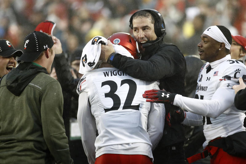 Cincinnati Bearcats coach Luke Fickell hugs safety James Wiggins (32) after Wiggins intercepted a pass during the Military Bowl on Dec. 31, 2018. (Getty)