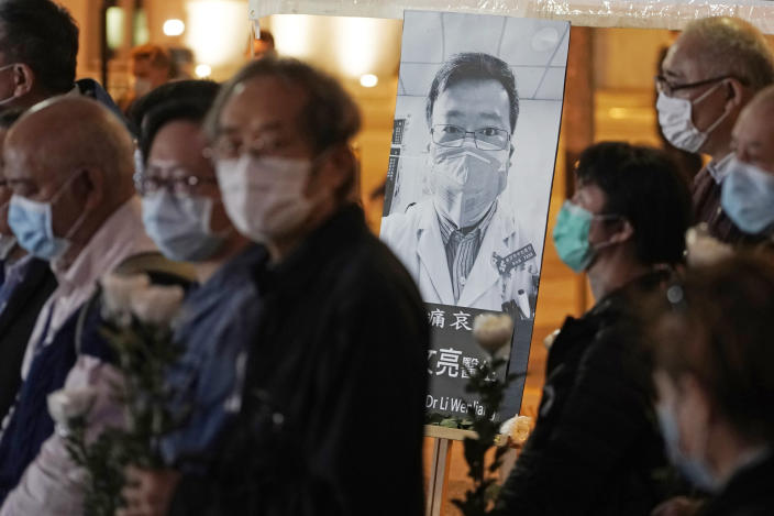 FILE - In this Feb. 7, 2020 file photo, people wearing masks attend a vigil for Chinese doctor Li Wenliang, in Hong Kong. The outpouring of grief and rage sparked by Li's death was an unusual - and for the Chinese Communist Party, unsettling - display in China's tightly monitored civic space. (AP Photo/Kin Cheung, File)