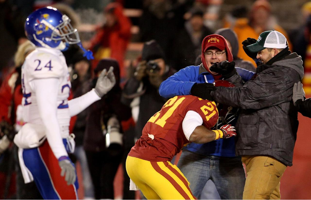 Iowa State running back Shontrelle Johnson is congratulated by fans in the back of the end zone after scoring a touchdown in the fourth quarter of their NCAA football game against Kansas in Ames, Iowa Saturday Nov. 23, 2013. (AP Photo/ Justin Hayworth)