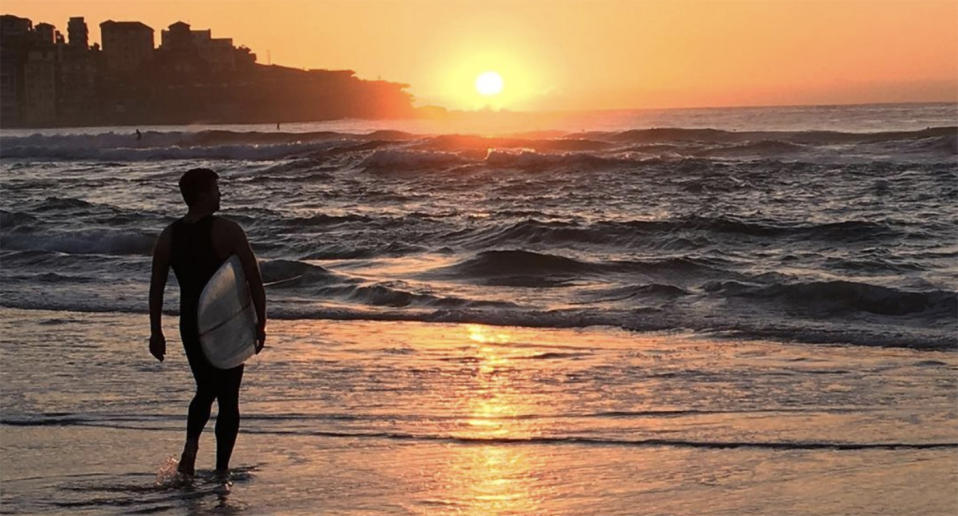 A surfer stands in the shallows at sunrise on Bondi Beach.