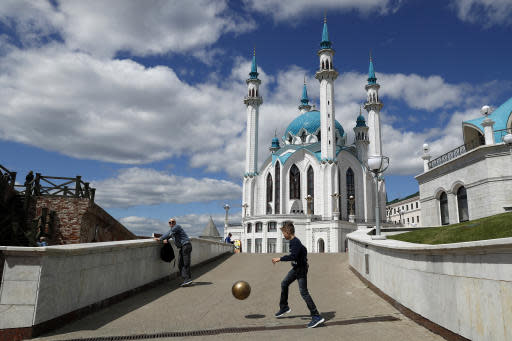 In this June 15, 2018 photo a boy plays in a ball near the Qolsharif Mosque, a day before the group C match between France and Australia at the 2018 soccer World Cup in the Kazan Arena in Kazan, Russia. (AP Photo/Pavel Golovkin)