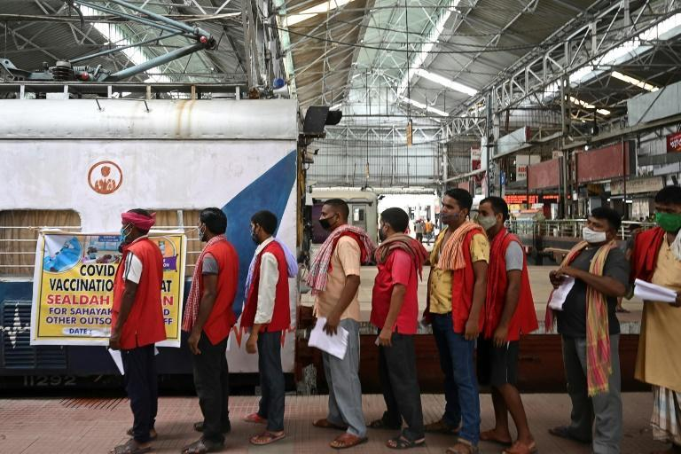 Railway porters wait to get doses of the Covishield vaccine against the Covid-19 coronavirus inside compartments modified as temporary vaccination centers at Sealdah railway station in Kolkata