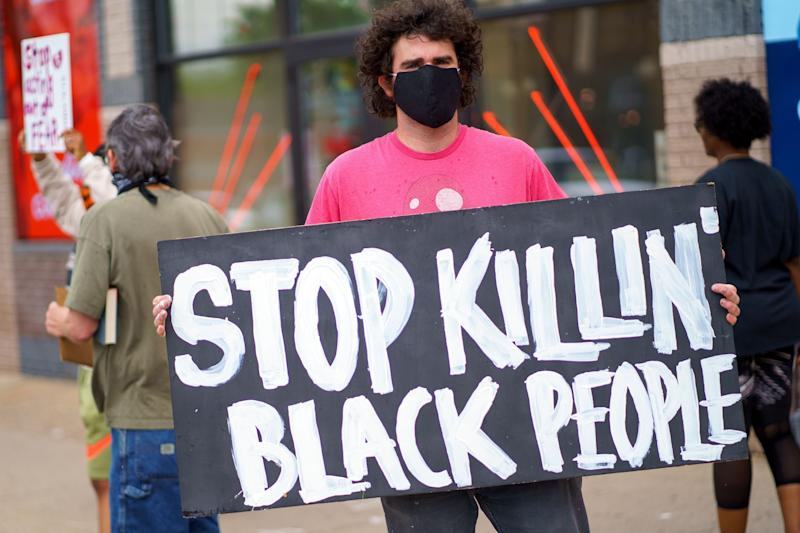 "A man holds a ""Stop Killing Black People"" sign on May 26, 2020, near the area where Minneapolis police killed George Floyd.  (Photo: KEREM YUCEL via Getty Images)"