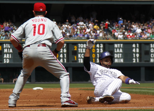 Colorado Rockies' Wilin Rosario, right, slides into third base after hitting an RBI-triple as Philadelphia Phillies third baseman Michael Young waits for the throw from the outfield in the first inning of a baseball game in Denver, Saturday, June 15, 2013. (AP Photo/David Zalubowski)