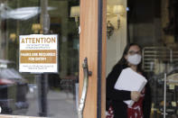A sign reminds customers to wear their masks at a bakery in Lake Oswego, Ore., on Friday, May 21, 2021. As the federal government and many states ease rules around mask-wearing and business occupancy, some blue states like Oregon and Washington are still holding on to some longtime coronavirus restrictions. (AP Photo/Gillian Flaccus)