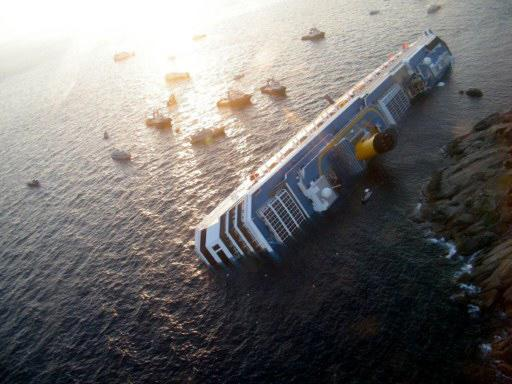 "View of the Costa Concordia on January 14, 2012, after the cruise ship ran aground and keeled over off the Isola del Giglio, last night. Three people died and several were missing after the ship with more than 4,000 people on board ran aground sparking chaos as passengers scrambled to get off. The ship was on a cruise in the Mediterranean, leaving from Savona with planned stops in Civitavecchia, Palermo, Cagliari, Palma, Barcelona and Marseille,"" the company said. AFP PHOTO / FILIPPO MONTEFORTE"