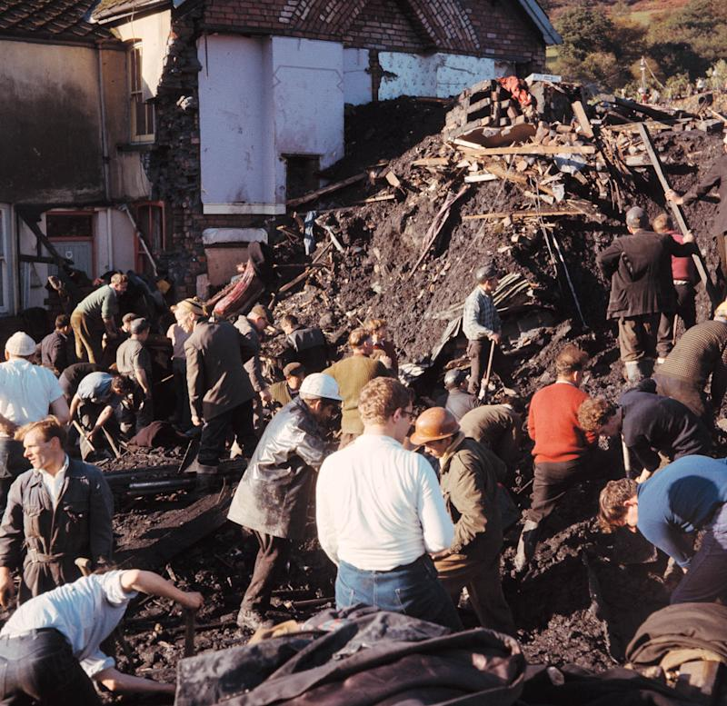 Rescue workers toil in a huge pile of rubble beside the school, after the collapse of a slag-tip at Aberfan, Wales, Oct. 22, 1966. Many of the local schoolchildren were kiled when the rubble engulfed the village school. (AP Photo)