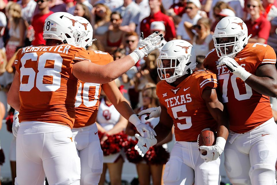DALLAS, TEXAS - OCTOBER 09: Bijan Robinson #5 of the Texas Longhorns is congratulated after a touchdown run in the first quarter against the Oklahoma Sooners during the 2021 AT&T Red River Showdown at Cotton Bowl on October 09, 2021 in Dallas, Texas. (Photo by Tim Warner/Getty Images)