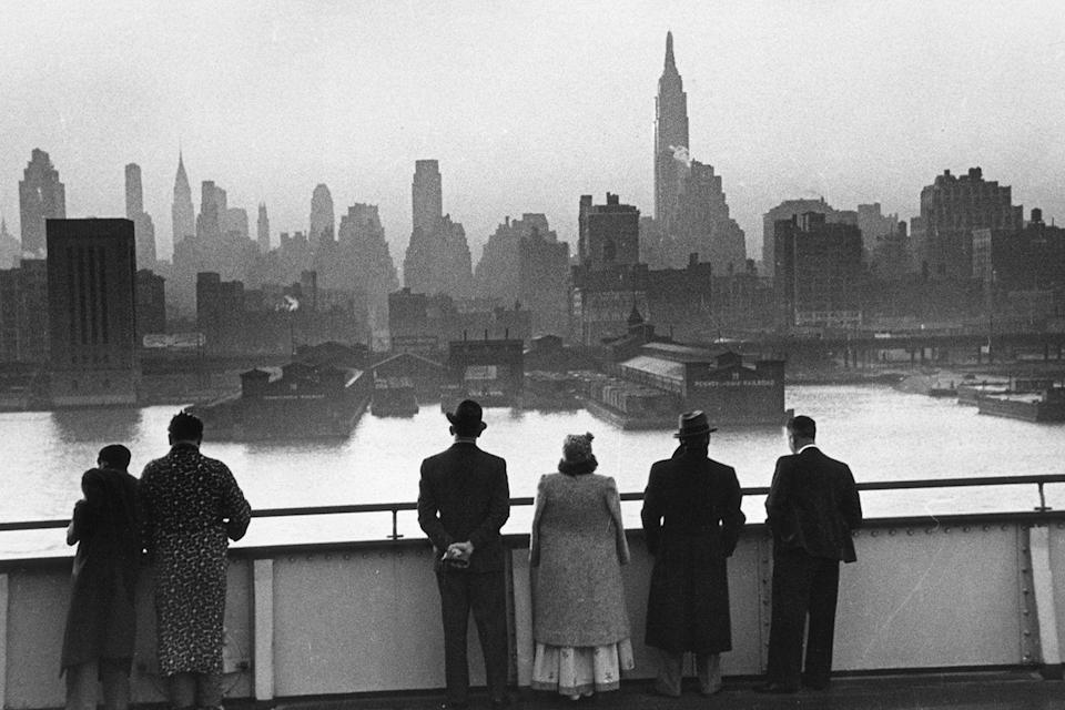 <p>Passengers on board the Cunard White Star liner Queen Mary view the New York skyline as the ship docks in Manhattan at dawn. </p>