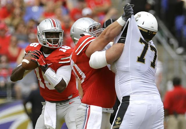 Ohio State quarterback J.T. Barrett, left, looks for a receiver as center Jacoby Boren blocks Navy guard Bernard Sarra during the first half of an NCAA college football game in Baltimore, Saturday, Aug. 30, 2014. (AP Photo/Patrick Semansky)