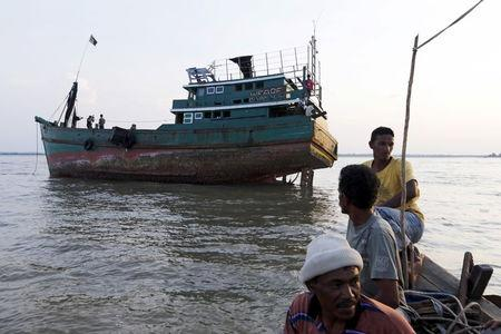 Acehnese fishermen pass near an abandoned boat which carried Rohingya and Bangladeshi migrants from Thailand, found off the coast near the city of Kuta Binje, Indonesia's Aceh Province May 20, 2015.  REUTERS/Beawiharta
