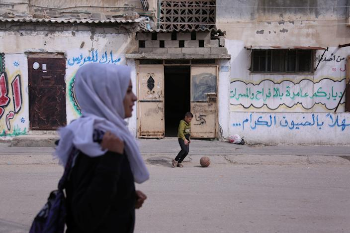 "A boy plays with a ball as Palestinian high school student Wessal Abu Amra, 17, walks home from school in Gaza City on Feb. 14, 2019. ""Despite wars and the bad economy, we are trying to find some joy,"" said Abu Amra, who says she loves shopping and eating fast food in Gaza with her friends. ""We know the reality we live in so we do things we love to get out of a bad mood."" (Photo: Samar Abo Elouf/Reuters)"
