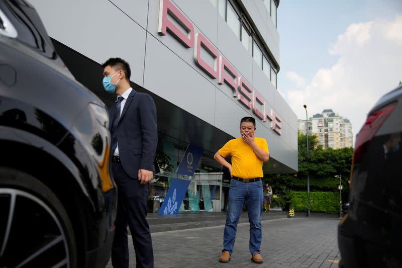 Guo Hui looks at his Porsche Cayenne he is selling to pay his debts, at a car dealership in Guangzhou