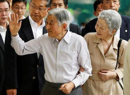 Japan's Emperor Akihito, flanked by Empress Michiko, waves to well-wishers as they board a Shinkansen bullet train to depart to their imperial summer villa in Nasu, at Tokyo station in Tokyo