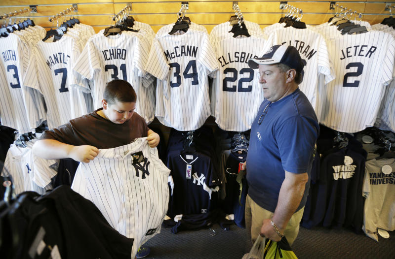 Phil Castinetti, of Boston, Mass., watches his son Cory, left, try on a New York Yankees jersey after watching a spring training baseball practice Tuesday, Feb. 18, 2014, in Tampa, Fla. (AP Photo/Charlie Neibergall)
