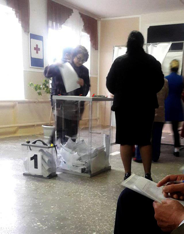 Voter Ludmila Sklyarevskaya, who denied voting multiple times, casts a ballot at a polling station number 215 during the presidential election in Ust-Djeguta, Russia March 18, 2018. Picture taken March 18, 2018. REUTERS/Polina Nikolskaya