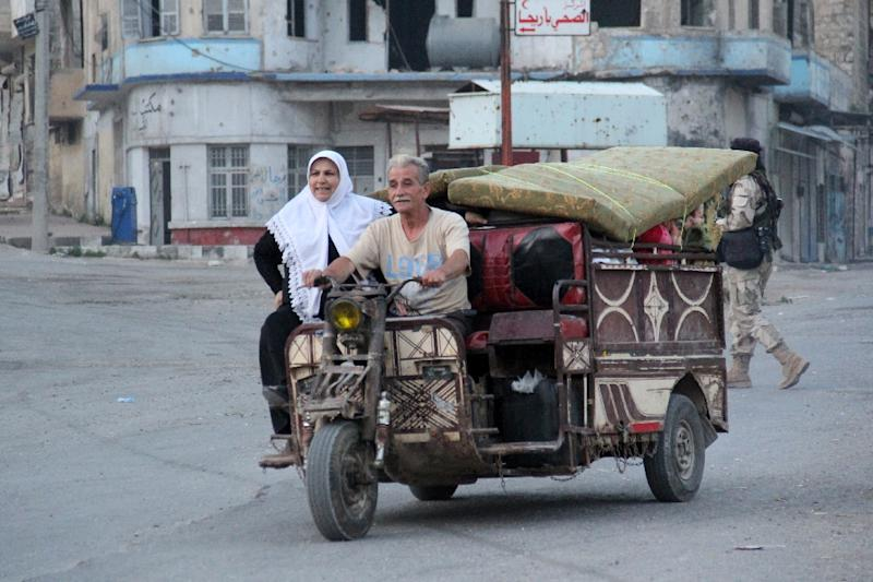 A couple rides a three-wheeled vehicle loaded with their belongings on May 29, 2015 as they flee the Syrian town of Ariha, in the northwestern province of Idlib, a day after the city was seized by a rebel coalition led by Al-Qaeda's Syria franchise (AFP Photo/Omar Haj Kadour)