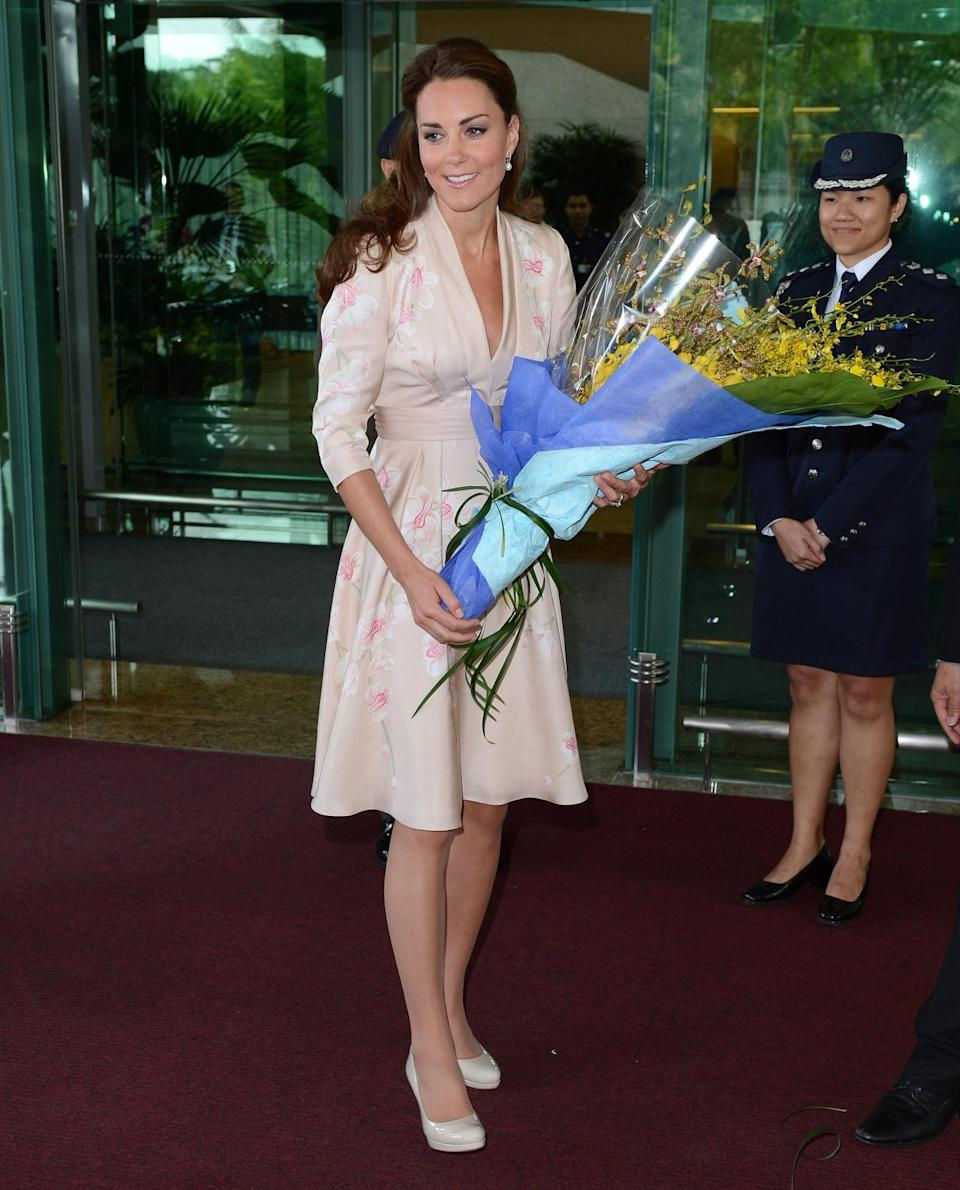 <p>Kate wore a pale pink Jenny Packham dress for her arrival into Singapore. She accessorised with patent pumps from L.K. Bennett and a matching bag. </p><p><i>[Photo: PA]</i></p>